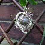 an agate bead surrounded by silver wire and pearls
